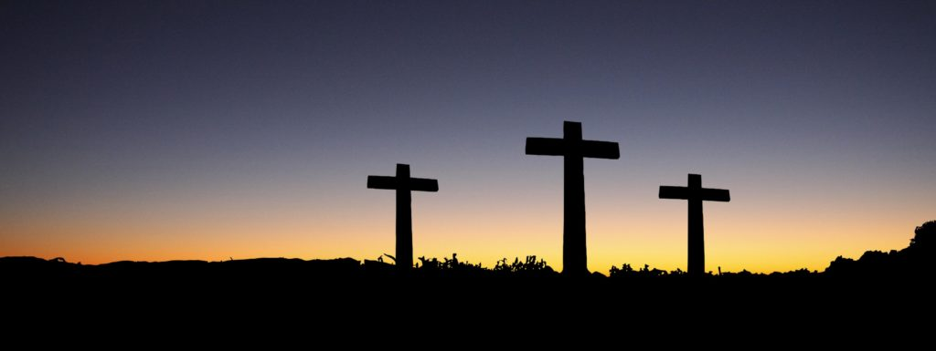 Three crosses in silhouette at dawn.